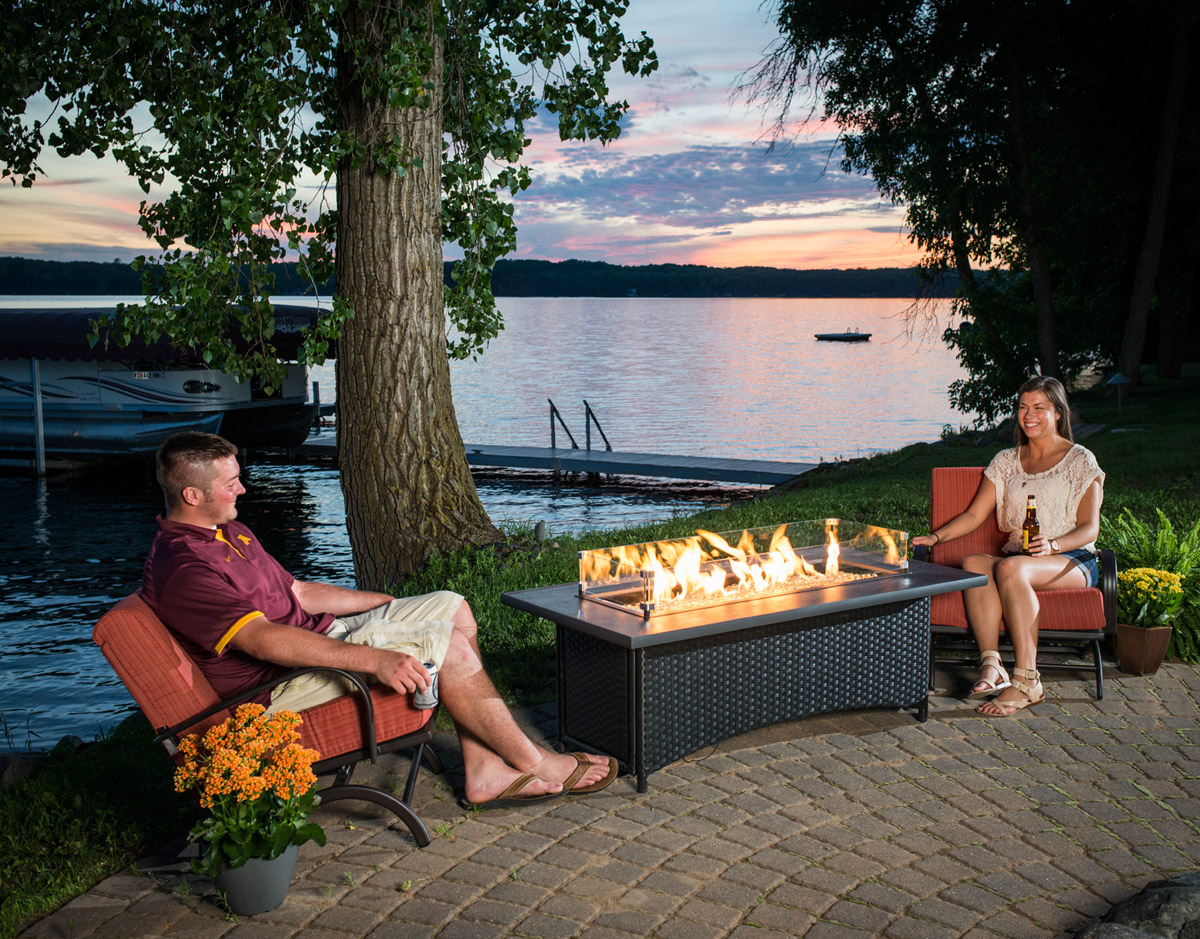 outdoor patio furniture fire pit table chair sunset montego water lake boat tree sunset pier paved paver